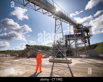 Worker standing under conveyor in quarry - Stock Photo