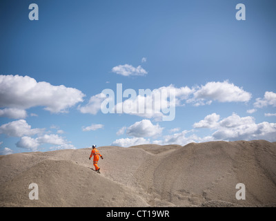 Worker climbing sand dunes in quarry - Stock Photo