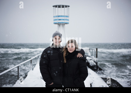 Couple hugging on snowy pier - Stock Photo