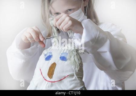 Girl cutting dolls hair - Stock Photo