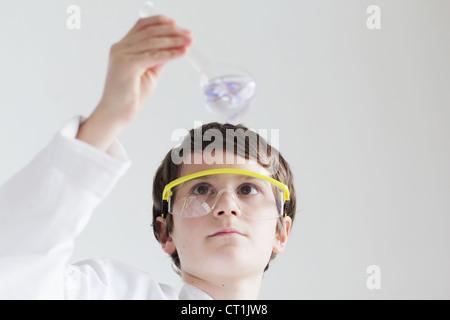 Student examining beaker of liquid - Stock Photo