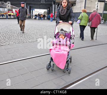 Berlin, Germany. Woman pushing child in pushchair / buggy - Stock Photo