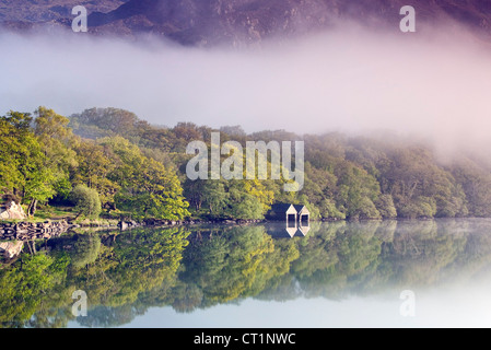 Boathouse on tree lined north western shore of a misty Llyn Dinas Lake in the Nantgwynant Valley Snowdonia North - Stock Photo