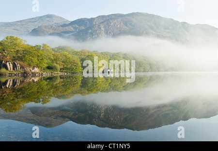 Mountains above a tree lined shore misty dawn on Llyn Dinas Lake in the Nantgwynant Valley Snowdonia National Park - Stock Photo