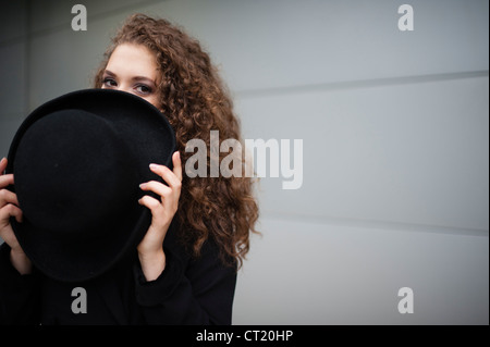 A young 20 year old slim attractive woman girl hiding her face behind a big black hat UK - Stock Photo