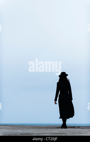 A rear view of a woman girl wearing a long black coat and hat walking away into the mist - Stock Photo