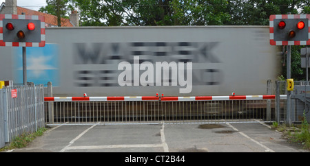 Railway tracks red flashing warning light sign level crossing barrier gates country road container train motion - Stock Photo
