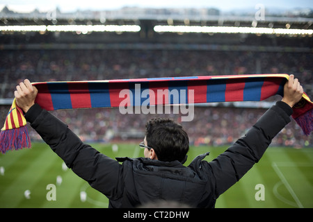 FC Barcelona fan holding a scarf with the colours of his team during a match in Camp Nou stadium - Stock Photo