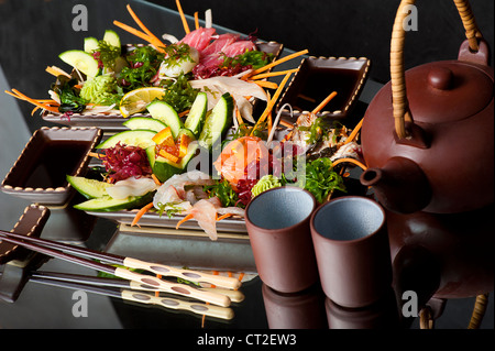 Mixed sashimi, raw fish with cucumber on traditional japanese plate. soy sauce and clay teapot and cups - Stock Photo