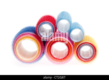 Colorful hair rollers stacked and isolated on white background - Stock Photo