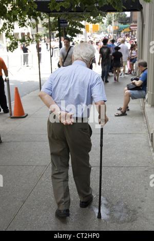Old man shuffling along in the Lenoxhill neighborhood of Manhattan. - Stock Photo