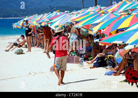 Colourful beach umbrellas and deckchairs for a summer holiday on the tropical sandy beach of Khai Nai Island, Phuket, - Stock Photo