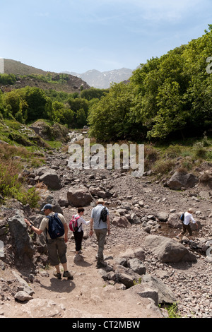 Tourists walking in the HIgh Atlas cross a dried up river bed, near Imlil, Morocco, Africa - Stock Photo