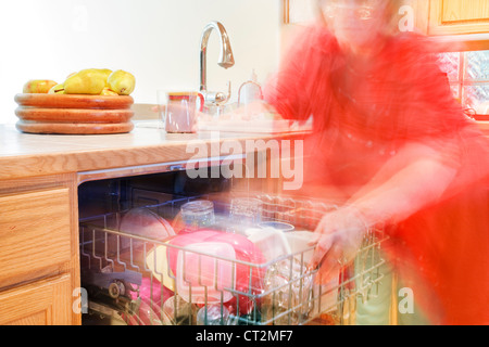Woman busily moving about - getting things out of the dishwasher - Stock Photo