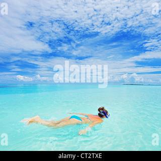 A woman with snorkeling mask diving in Kuredu resort, Maldives island, Lhaviyani atoll - Stock Photo