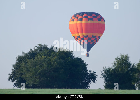 Hot air Balloon flies over Polk County, Florida in the early morning. - Stock Photo