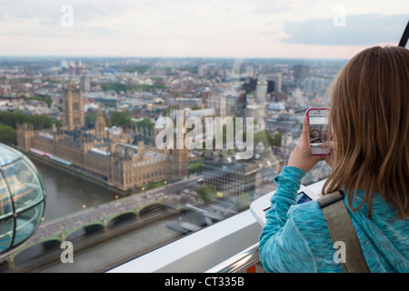 A young girl takes a photo from the London Eye