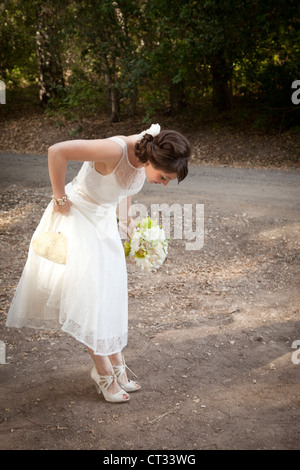 Bride with flowers looking down at her shoes. - Stock Photo