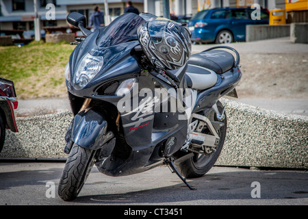 A Suzuki Hayabusa parked with a helmet in the handlebar - Stock Photo