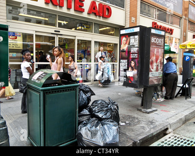 sidewalk street  scene busy 8th Avenue corner on a hot summer day in midtown Manhattan New York City - Stock Photo