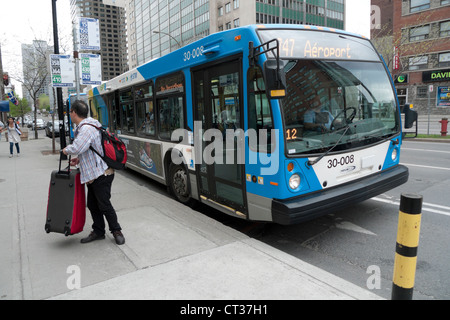 Asian passenger being let off at a bus stop by the 747 Trudeau Airport bus on Boul. René-Lévesque Montreal Quebec - Stock Photo