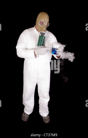 Man in hazard suit and wearing a gas mask, holding a glass container of blue chemical that is giving off a gas or - Stock Photo