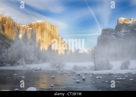 Alpenglow on the granite peaks in Yosemite valley with mist rising above the Merced river - Stock Photo