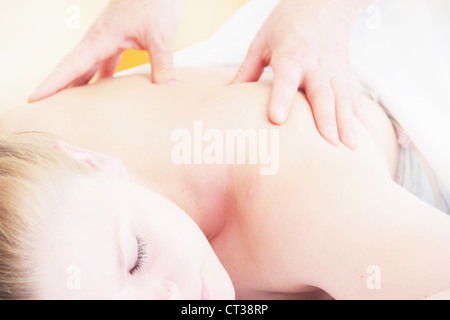 Woman having back massage in spa - Stock Photo