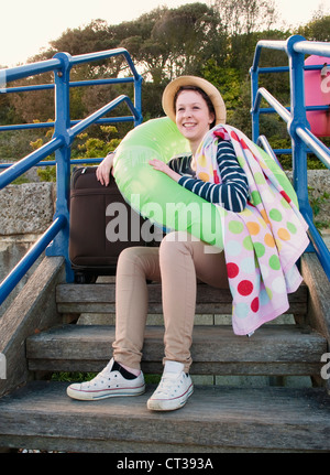 Teenage girl with suitcase on steps - Stock Photo