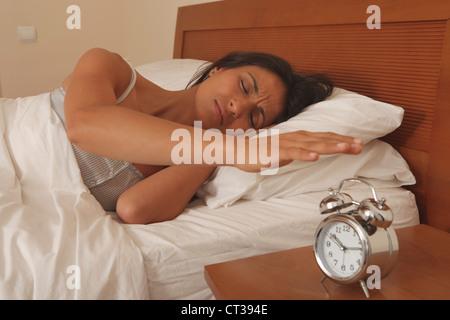 Woman turning off alarm clock - Stock Photo