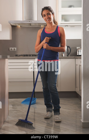 Smiling woman cleaning kitchen floor - Stock Photo