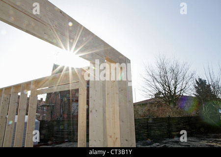 Sun shining on new building on site - Stock Photo