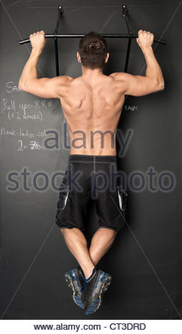 Man doing pull ups in gym - Stock Photo