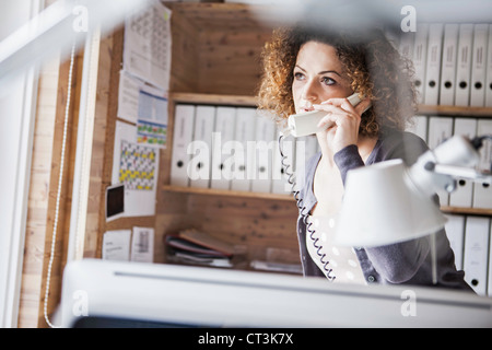 Businesswoman talking on phone in office - Stock Photo