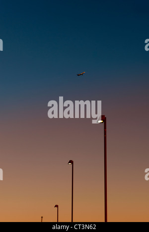Airplane over street lights at dusk - Stock Photo