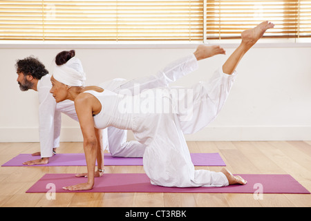 Couple practicing yoga in class - Stock Photo