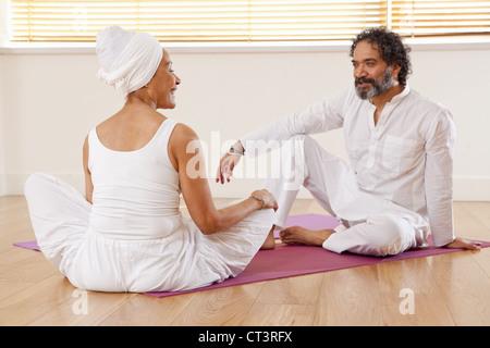 Couple talking on yoga mats - Stock Photo