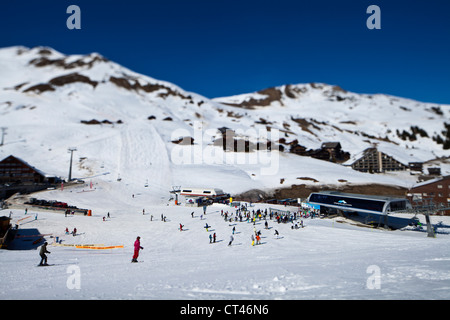 Tilt-shift photo of skiers making their way to the chair lifts in Les Crosets, Switzerland. - Stock Photo