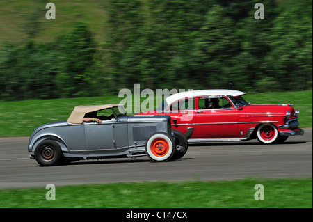 Two hotrods racing. Motion blur on wheels and background - Stock Photo