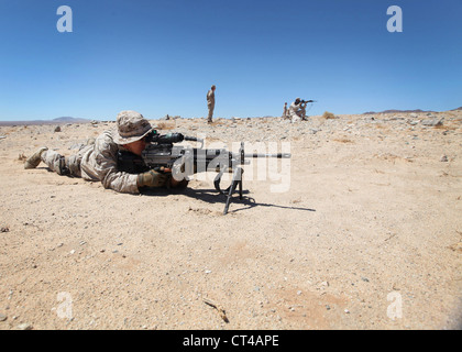 A Marine with 1st Law Enforcement Battalion, I Marine Expeditionary Force, aims an M249 Squad Automatic Weapon down - Stock Photo