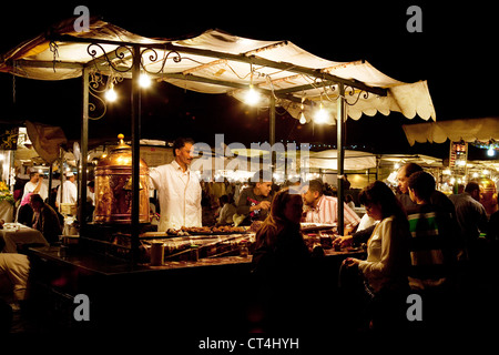 Local people eating street food at food stalls in Djemaa el Fna square at night, Marrakech Morocco Africa - Stock Photo