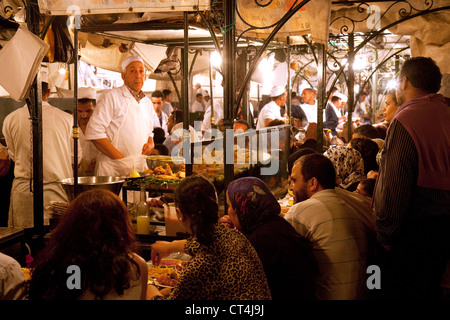 People eating street food at food stalls in Djemaa el Fna square at night, Marrakech Morocco Africa - Stock Photo