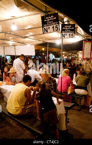 Tourists eating at food stalls in Djemaa el Fna square at night, Marrakech Morocco Africa - Stock Photo