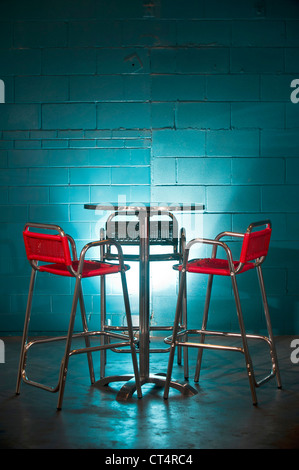 Brightly colored orange chairs and table in front of a turquoise wall. - Stock Photo