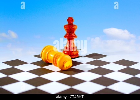 Two chess kings on board, one standing, one lying down, blue sky and white clouds background - Stock Photo