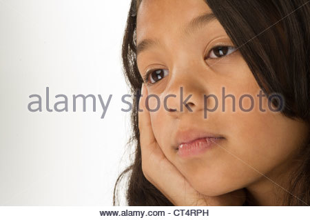 close up an 11 year old girl looking sad or reflective - Stock Photo