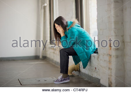 young girl sitting on a window sill with head in hands looking depressed. - Stock Photo
