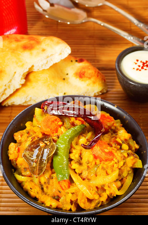 Indian vegetarian meal of spicy lentil dal, with chillies, naan bread and yogurt. - Stock Photo