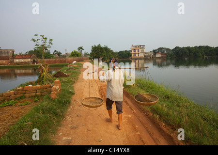 A Vietnamese farmer walks along a dirt road on September 3, 2010 in Duong Lam Village, Vietnam. The Ancient village, - Stock Photo