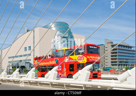 The Samual Beckett Bridge with a Dublin city 'hop on hop off' tour bus driving across. - Stock Photo